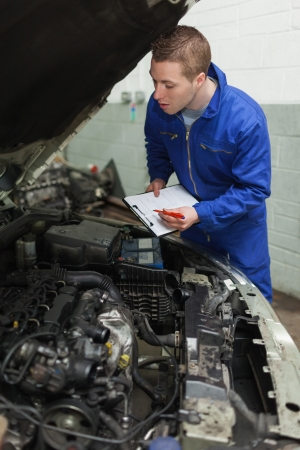 auto mechanic: Mechanic preparing checklist while looking at car engine Stock Photo