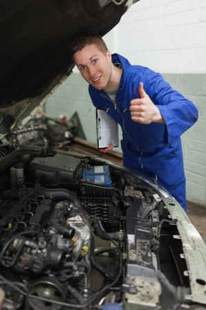 bonnet up: Portrait of confident mechanic by car with open hood gesturing thumbs up