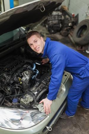 auto mechanic: Portrait of male mechanic examining car engine