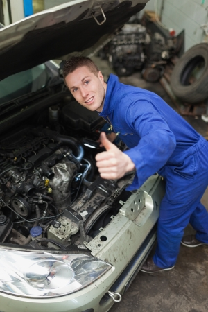 bonnet up: Portrait of auto mechanic by car showing thumbs up sign