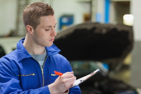 noting: Male mechanic writing on clipboard in workshop
