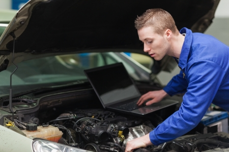 Car mechanic with laptop repairing engine photo