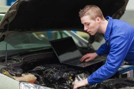 garage automobile: M�canicien de v�hicule avec moteur r�paration d'ordinateur portable Banque d'images