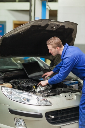 Auto mechanic with laptop repairing car engine in workshop Stock Photo - 18109633