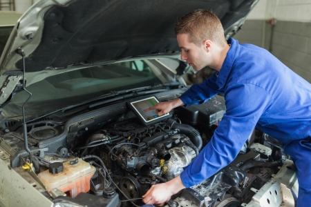 garage automobile: Mécanicien Homme avec moteur tablette numérique réparation voiture Banque d'images