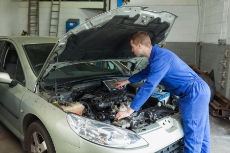 Male mechanic examining car engine with the help of digital tablet photo
