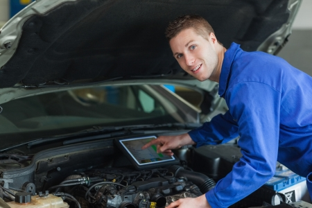 Portrait of confident mechanic by car using digital tablet photo