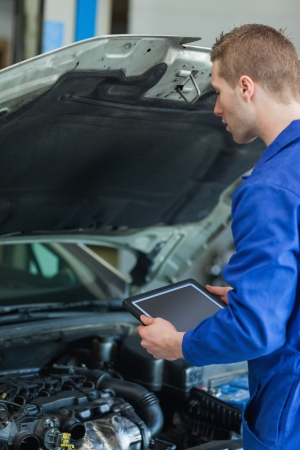 Male mechanic with digital tablet examining car engine photo