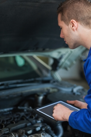 Male mechanic using digital tablet while examining car engine photo