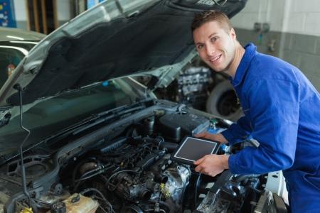garage automobile: Portrait d'un mécanicien hommes heureux en voiture tenant tablette numérique Banque d'images