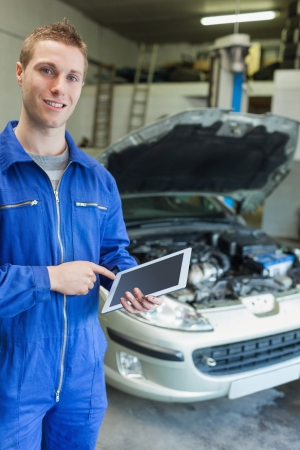 Portrait of happy mechanic using tablet computer with car in background photo