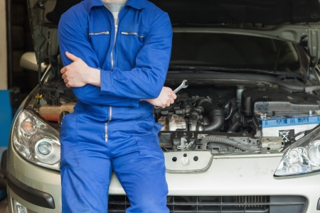 auto mechanic: Male mechanic in front of car with open hood Stock Photo