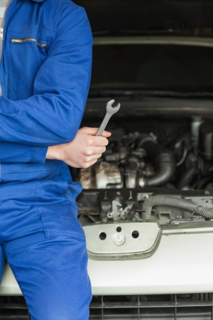Male mechanic with spanner leaning on car Stock Photo - 18110435
