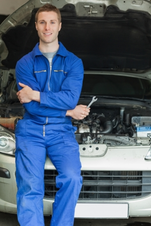 Portrait of happy mechanic leaning on car engine Stock Photo - 18110430