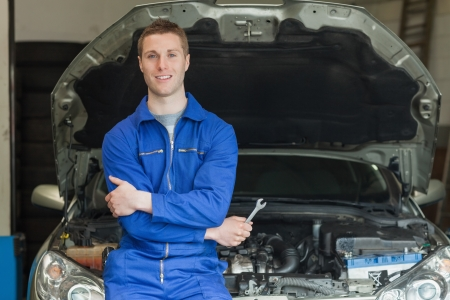 Portrait of confident mechanic leaning aganist car with open hood Stock Photo - 18110426