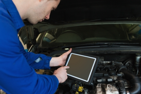 car garage: Auto mechanic by car with open hood using digital tablet