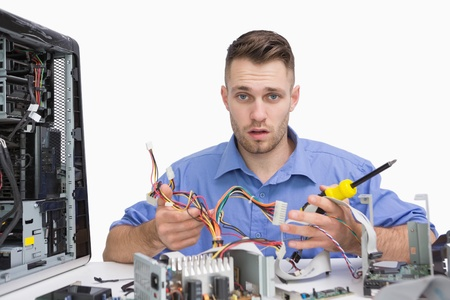 Portrait of young computer engineer working on cpu parts over white background photo