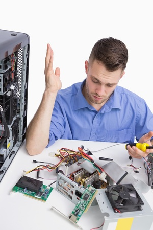 Confused young computer engineer fixing computer parts over white background photo