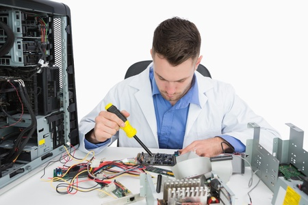 Young computer engineer working on cpu parts over white background photo
