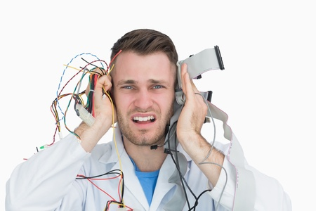 Close-up portrait of young it professional yelling with cables in hands photo