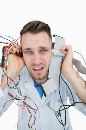 Close-up portrait of young it professional yelling with cables in hands over white background photo