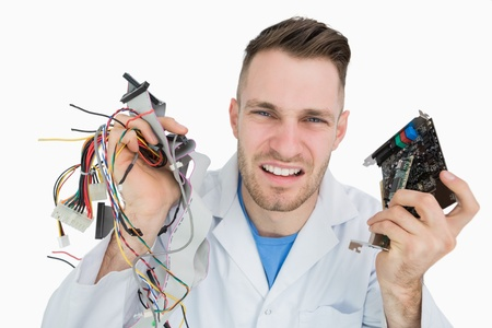 Portrait of young it professional yelling with cpu parts in hands over white background photo