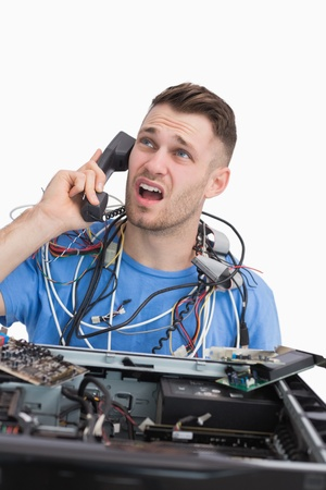 Young frustrated computer engineer on call in front of open cpu over white background Stock Photo - 18107766