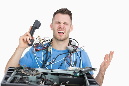 Young frustrated computer engineer on call in front of open cpu over white background photo