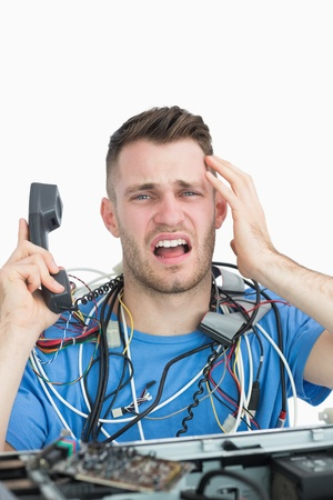 Portrait of young frustrated computer engineer on call in front of open cpu over white background Stock Photo - 18108068