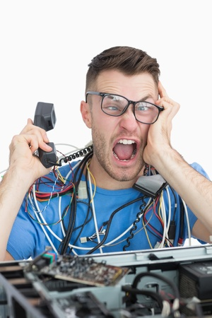 Portrait of frustrated computer engineer screaming while on call in front of open cpu over white background Stock Photo - 18108002
