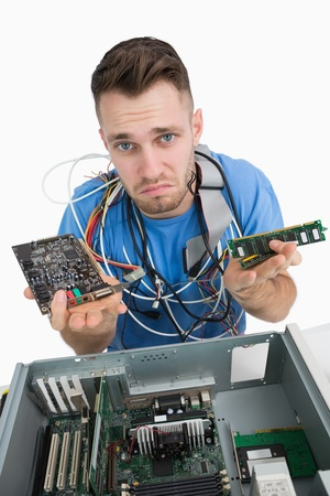 Portrait of confused young it professional with sound card and ram in front of open cpu over white background photo