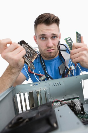 Portrait of confused young it professional with chips in front of open cpu over white background Stock Photo