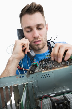 Young computer engineer working on sound card on cpu while on call over white background photo