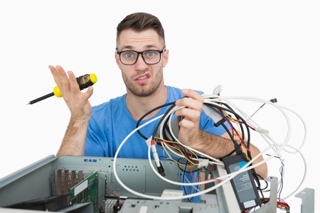 Portrait of confused young it professional with screw driver and cables in front of open cpu over white background photo