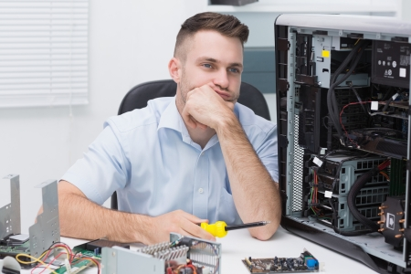Thoughtful hardware professional sitting by an open cpu at workplace