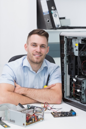 Portrait of smiling hardware professional sitting by an open cpu at workplace Stock Photo - 18108374