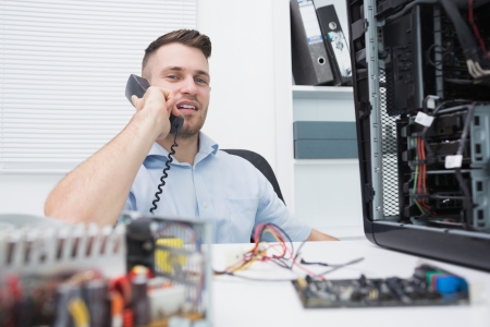 Portrait of hardware professional sitting by an open cpu while on call at workplace Stock Photo - 18108247