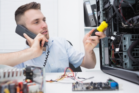 Young computer engineer working on cpu while on call at workplace Stock Photo - 18108421