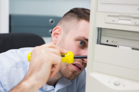it support: Close-up of young computer engineer with screw driver fixing cpu Stock Photo