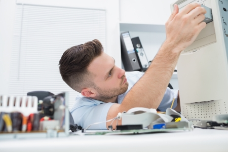 Young it professional repairing cpu on desk at workplace Stock Photo