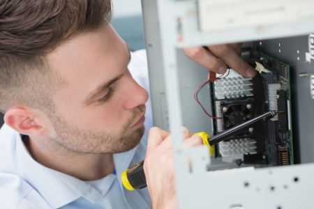 Close-up of young it professional fixing computer problem at workplace photo