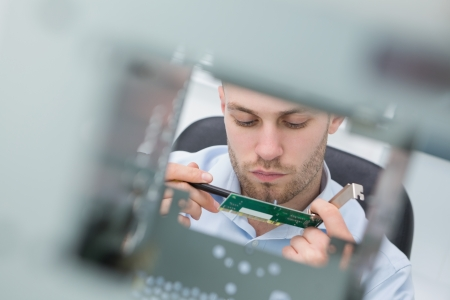 Close-up of young it professional with lan card working on cpu at workplace photo