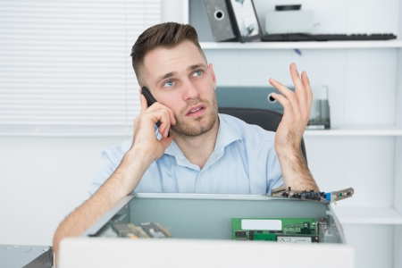 Young worried computer engineer on call in front of open cpu at workplace Stock Photo - 18107342