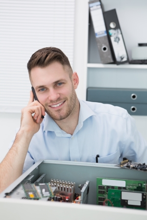 Portrait of young smiling computer engineer on call in front of open cpu at workplace Stock Photo - 18108283