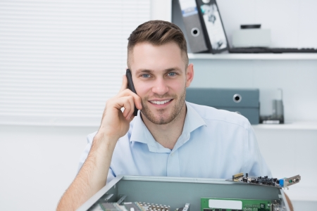 Portrait of young smiling computer engineer on call in front of open cpu at workplace Stock Photo - 18107871