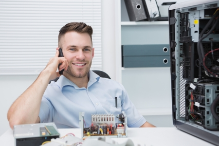 Portrait of young smiling computer engineer on call by open cpu at workplace Stock Photo - 18108076