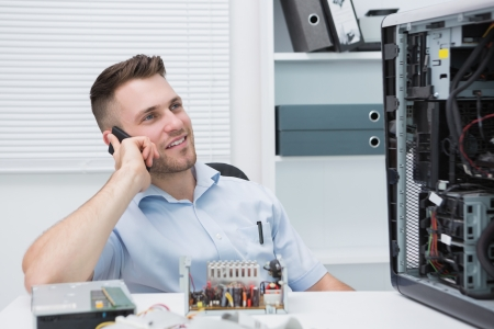 Young smiling computer engineer on call by open cpu at workplace Stock Photo - 18108058