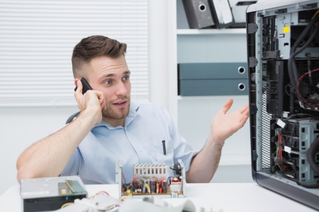 Young computer engineer on call as he gestures towards an open cpu at workplace Stock Photo - 18108111