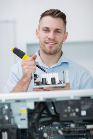 Portrait of young computer engineer working on cpu part in front of open cpu at workplace Stock Photo - 18107438