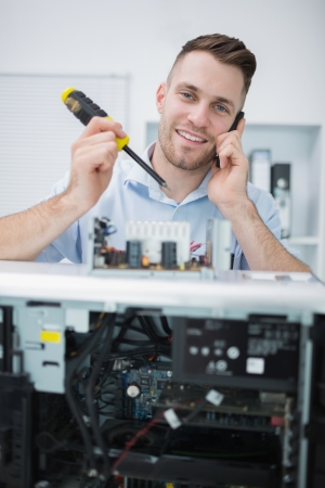 Portrait of young computer engineer working on cpu part in front of open cpu at workplace Stock Photo - 18107597